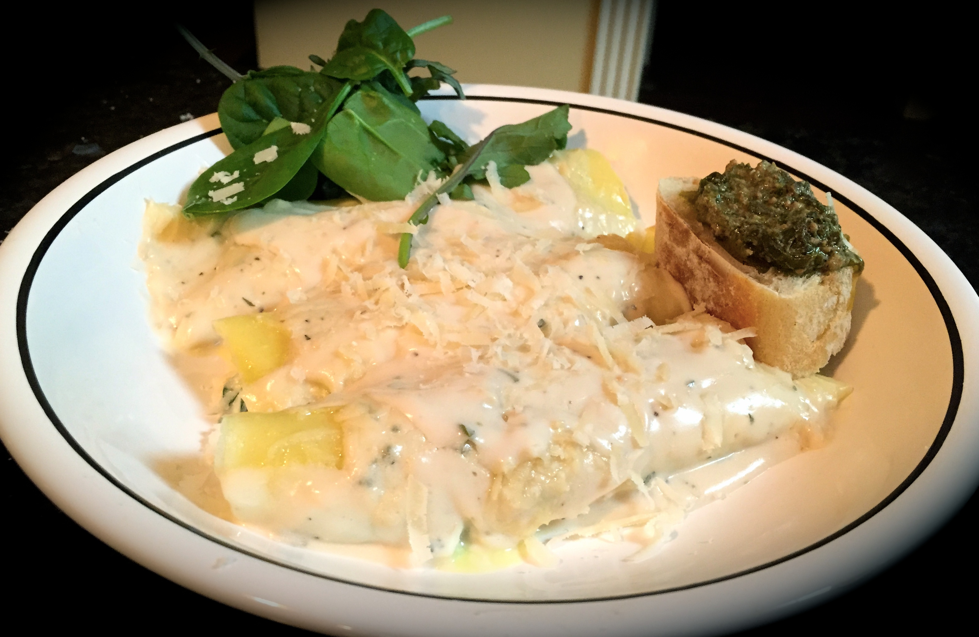 Spinach and cheese stuffed manicotti in alfredo sauce served with spinach salad and basil pesto crostino